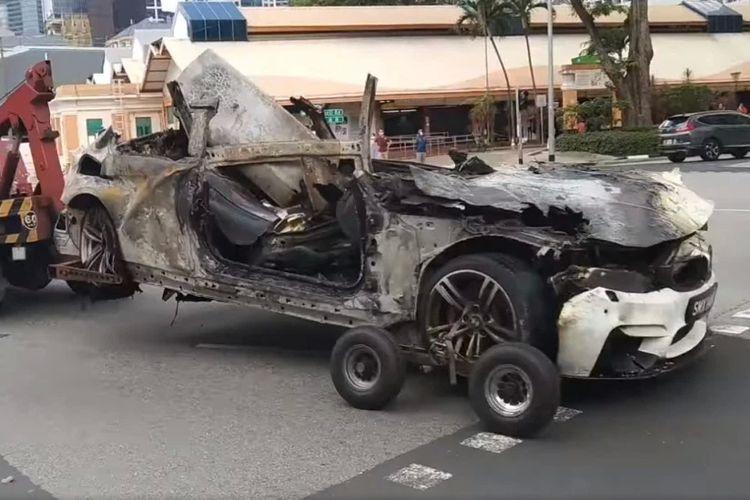 Tangkapan layar dari video yang menampilkan bangkai mobil sedan BMW putih, yang terbakar dan meledak dalam kecelakaan maut di Tanjong Pagar, Singapura, pada Sabtu (13/2/2021). Kecelakaan tunggal ini menewaskan semua 5 orang di dalam mobil.
