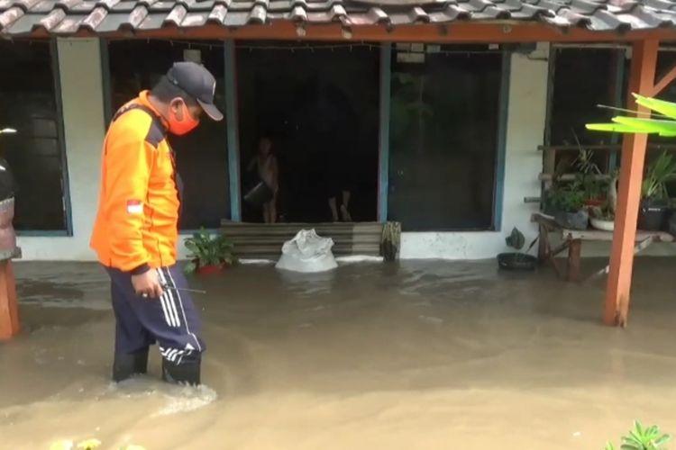 TERENDAM—Salah satu petugas BPBD Kabupaten Madiun meninjau rumah warga Desa Banjarsari, Kecamatan Madiun, Kabupaten Madiun yang terendam banjir pasca hujan selama delapan jam menerjang wilayah tersebut.