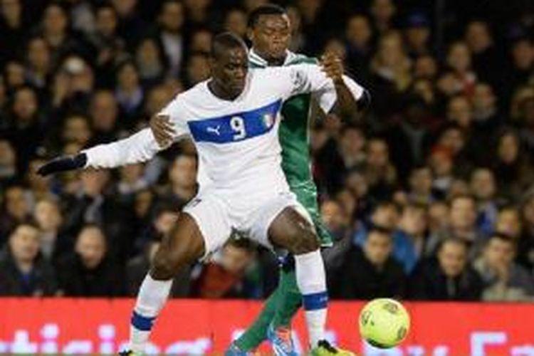 Penyerang Italia, Mario Balotelli berjibaku dengan salah seorang pemain Nigeria dalam pertandingan uji coba yang berlangsung di Stadion Craven Cottage, Fulham, London, Rabu (19/11/2013) dinihari WIB. Dalam pertandingan tersebut, kedua tim bermain imbang 2-2