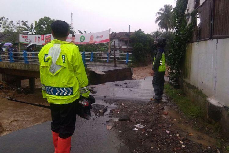 Petugas menjaga lokasi jembatan putus akibat banjir bandang di Desa Kalierang, Kecamatan Bumiayu, Brebes, Jawa Tengah, Rabu (25/4/2018).