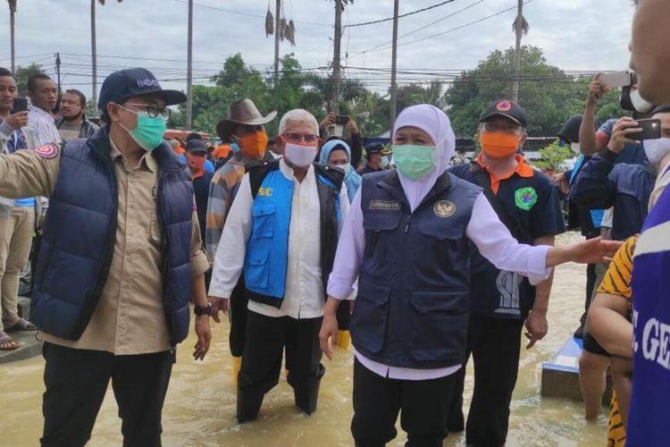 Bupati Pamekasan Baddrud Tamam bersama Gubernur Jawa Timur Khofifah Indar Parawansa saat meninjau kondisi banjir di Pamekasan, Sabtu (19/12/2020). Banjir di Pamekasan menewaskan 1 orang bocah karena terkena setrum saat bermain di luapan air sungai.
