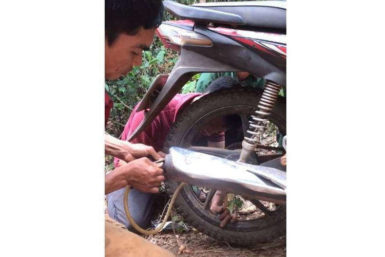 Tangkapan layar sejumlah pria sedang berupaya memompa ban sepeda motor menggunakan kompresi pembuangan knalpot.
