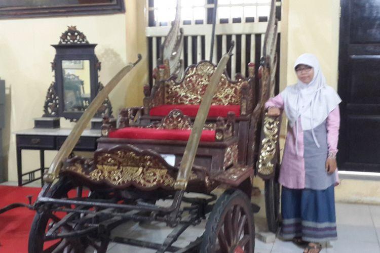 Seorang wisatawan saat berfoto bersama kereta kebesaran Arya Wiraradja yang usianya sudah hampir 1.000 tahun di Museum Keraton Sumenep, Minggu (2/7/2017).