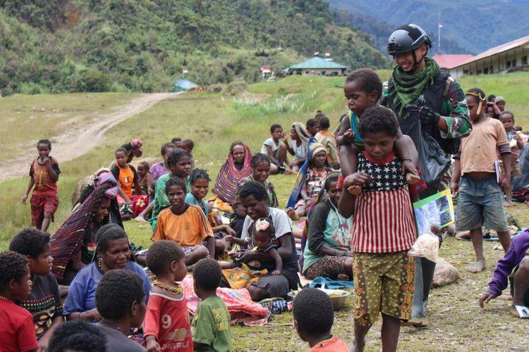 Tanpak prajurit TNI memberikan buku dan mengajak anak-anak di Distrik Mbua bermain games