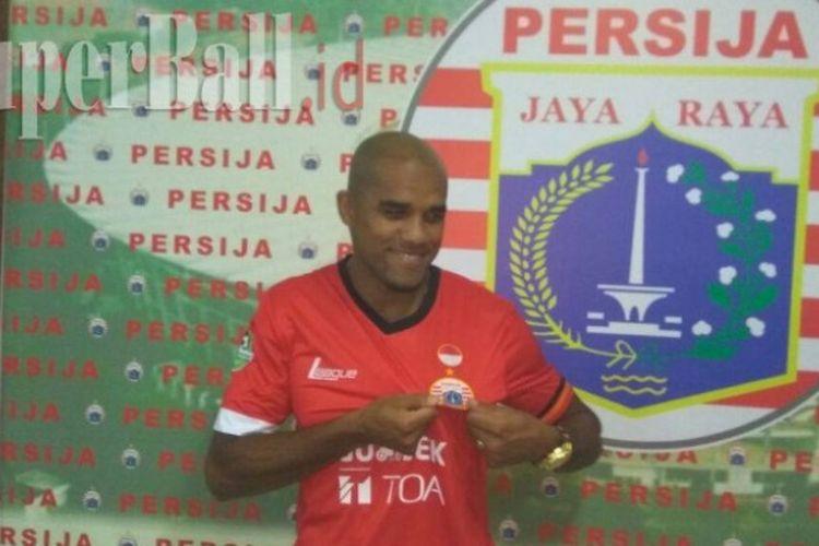 Pemain baru Persija Jakarta, Reinaldo Elias da Costa, berpose menggunakan kostum Persija.