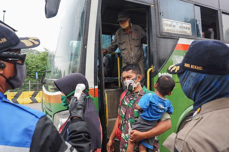 Petugas gabungan Polri dan Dishub melakukan pemantauan suhu tubuh penumpang bus yang turun di pintu tol Bekasi Timur, Bekasi, Jawa Barat, Rabu (15/4/2020). Pemberlakuan PSBB di Jawa Barat yang berlaku hari ini masih ada pengendara yang masih belum tertib dalam menjalankan arahan pengendalian COVID-19.