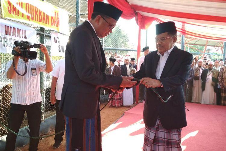 Wakil Presiden Jusuf Kalla saat menyerahkan sapi yang disumbangkan Presiden Jokowi ke Gubernur Sulawesi Selatan Nurdin Abdullah usai salat Idul Adha di Lapangan Karebosi Makassar, Minggu (11/8/2019).