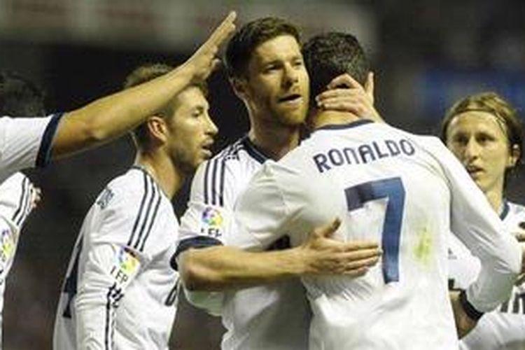 Penyerang Real Madrid dari Portugal, Cristiano Ronaldo (kedua dari kanan), merayakan gol keduanya dengan rekan setimnya, gelandang dari Spanyol, Xabi Alonso (tengah), dalam laga Liga BBVA melawan tuan rumah Athletic Bilbao di Stadion San Mames, Minggu (14/4/2013). Madrid akhirnya menang 3-0 dan Ronaldo memborong dua gol di antaranya. Satu gol lagi disumbangkan Gonzalo Higuain.