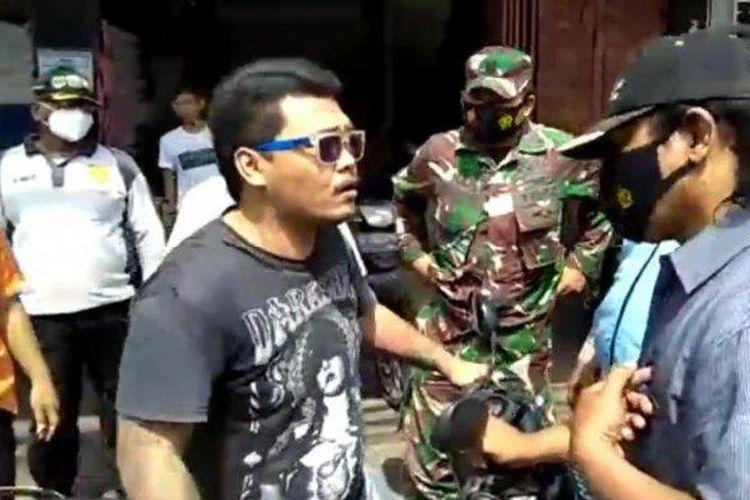 Seorang pria menolak sanksi razia masker saat petugas gabungan mendatanginya di Jalan Tanah Merdeka, Rambutan, Ciracas, Jakarta Timur, Kamis (4/3/2021)