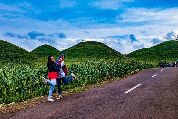 Pengunjung berfoto dengan latar belakang Bukit Teletubbies di Gunung Bagus