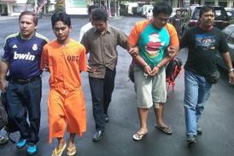 Tersangka pembobolan villa bule I Komang Putra Sanjaya alias Kasob (kanan) harus dipapah polisi karena betisnya mengalami luka tembak.
