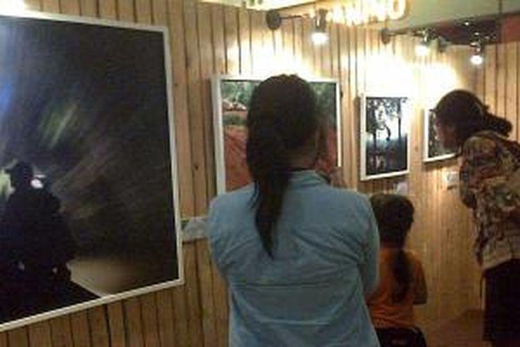 Pengunjung melihat pameran foto 'Melihat Indonesia, Ekspedisi Sabang-Merauke: Kota dan Jejak Peradaban' di lantai dasar Food Society Kota Kasablanka, Jakarta, Senin (30/12/2013) malam. Pameran ini akan terselenggara hingga 5 Januari 2014.