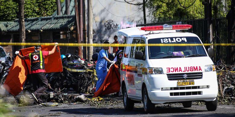 Petugas kepolisian saat mengevakuasi jenasah di depan Gereja Pantekosta Pusat Surabaya (GPPS) di Jalan Arjuna, Surabaya, Jawa Timur, Minggu (13/5/2018). Hingga pukul 12.30 WIB, jumlah korban ledakan di 3 gereja mencapai 10 korban meninggal dan 41 luka-luka.