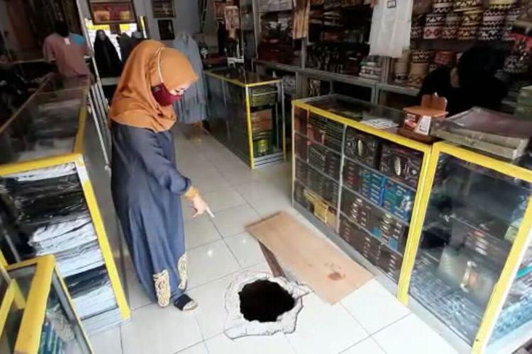 Pemilik toko batik lampung, Layla menunjukkan lubang yang dibuat pencuri untuk masuk ke tokonya. Pencuri menggali lubang ini dari saluran drainase yang ada di depan toko.