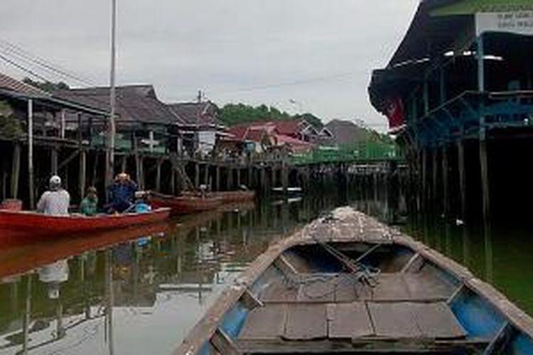 Perahu warga melintasi rumah-rumah panggung di Bontang Kuala, Bontang, Kaltim, Sabtu (8/8/2015). Warga Bontang kerap menyebut kampung ini sebagai 'Venice van Borneo'.