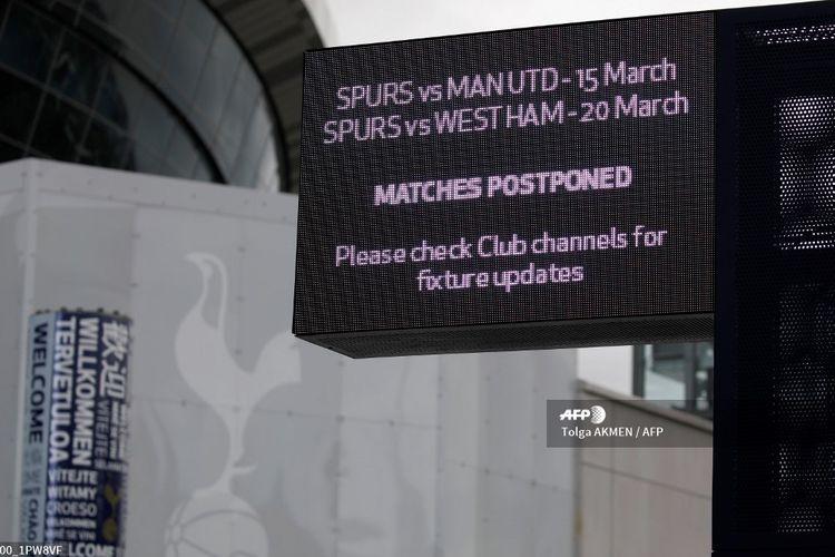 Papan informasi di dekat Tottenham Hotspur Stadium di London pada 15 Maret 2020 menunjukkan jadwal pertandingan Liga Inggris yang ditunda karena penyebaran virus corona.