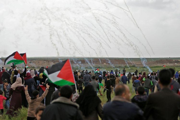 Warga Palestina dalam aksi unjuk rasa di perbatasan Jalur Gaza berlari menghindari tembakan gas air mata yang diluncurkan melalui drone milik militer Israel, Jumat (30/3/2018).