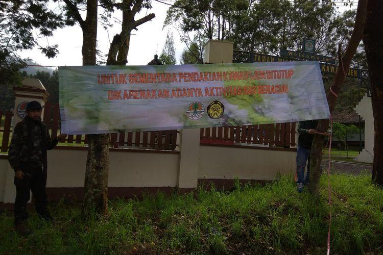 Petugas memasang banner larangan untuk mendaki Gunung Ijen. Banner dipasang di beberapa titik di Paltuding