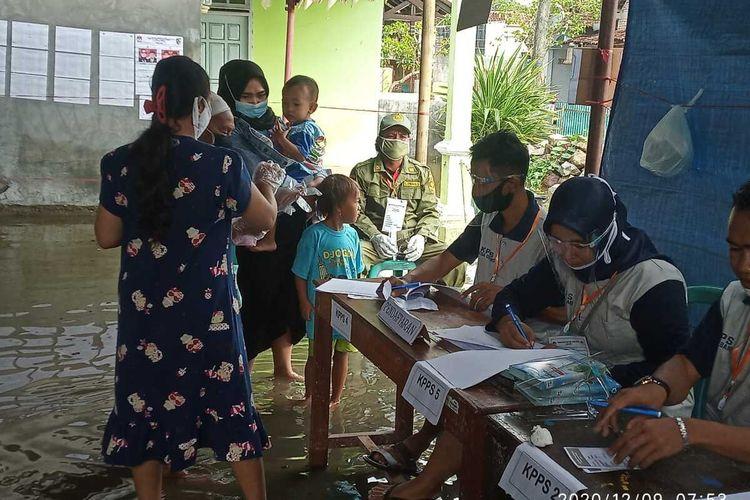 Warga menggunakan hak pilihnya di TPS 09 Desa Gebang Kecamatan Bonang Kabupaten Demak Jawa Tengah yang terendam banjir rob, Rabu (9/12/2020)