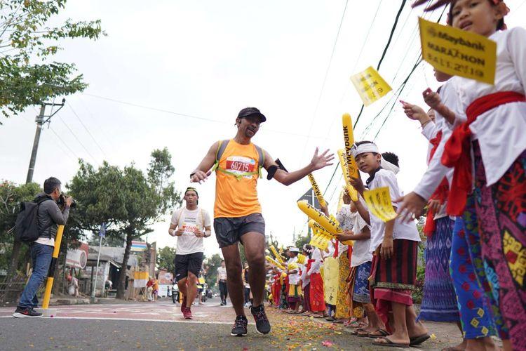 Warga Kabupaten Gianyar menyambut hangat para peserta lomba lari Maybank Marathon Bali 2019, Minggu (8/9/2019). Total ada lebih dari 11.600 peserta dari 50 negara yang turut serta dalam lomba lari internasional tahunan yang digelar untuk kedelapan kalinya ini.