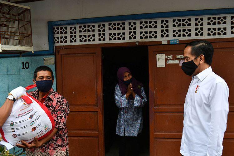 Presiden Joko Widodo (kanan) meninjau proses distribusi sembako tahap ketiga bagi masyarakat kurang mampu dan terdampak COVID-19 di kawasan Johar Baru, Jakarta Pusat, Senin (18/5/2020). Dalam blusukan ini, Presiden Jokowi ingin mengecek langsung penyaluran sembako pada masyarakat setempat.