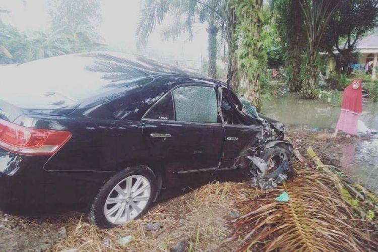 Seorang warga melihat mobil Camry yang ditumpangi Ibu dari Bupati Dharmasraya Sutan Riska Tuanku Kerajaan yang mengalami ringsek di bagian depan sebelah kanan, Kamis (12/12/2019).