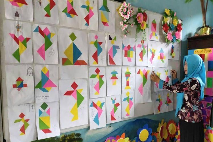 Tangram buatan siswa dipajang di mading kelas dan dipamerkan oleh guru secara daring kepada siswa dan orangtua siswa di rumah.