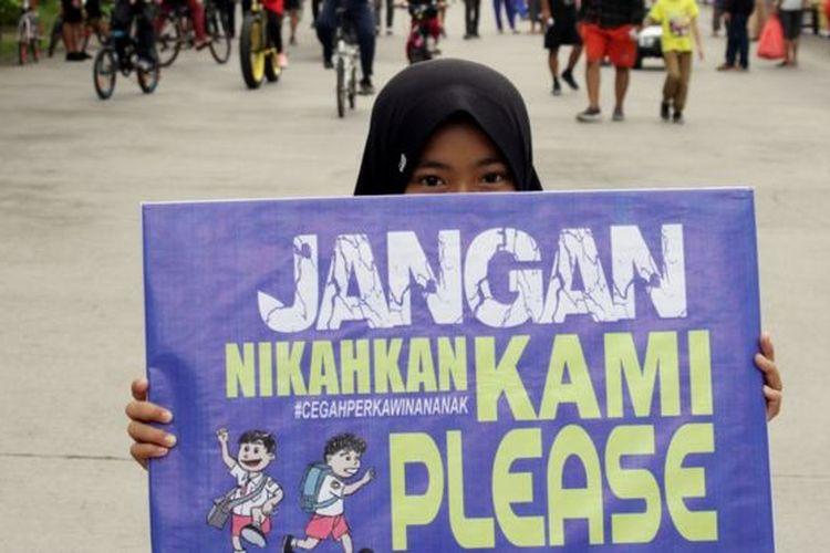 Seorang anak membawa poster saat aksi peringatan Hari Perempuan Internasional di Makassar, Sulawesi Selatan, Minggu (8/3). Aksi tersebut untuk mensosialisasikan pencegahan perkawinan anak guna menekan angka perkawinan usia dini yang masih marak terjadi.