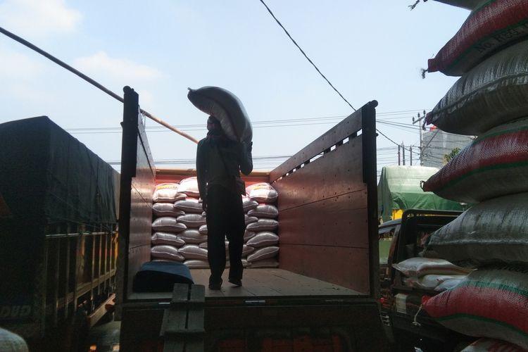 Seorang pekerja tengah melakukan aktivitas bongkar muat beras di pertokoan beras Pasar Johar Karawang, Kamis (18/3/2021).