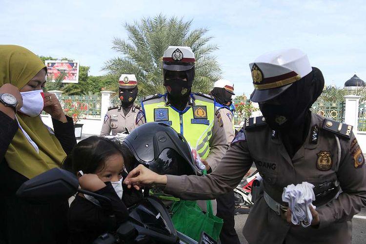 Polisi wanita (Polwan) jajaran Direktorat Lalu Lintas Polda Aceh membagikan masker gratis kepada pengguna kendaraan di ruas jalan depan Masjid Raya Baiturrahman, Kota Banda Aceh, Selasa (1/9/2020). Pembagian 1.000 masker gratis tersebut dalam rangka memperingati HUT ke-72 Polwan serta mendukung program Gebrakan Memakai Masker Gratis (Gemas) yang diluncurkan Pemerintah Aceh.