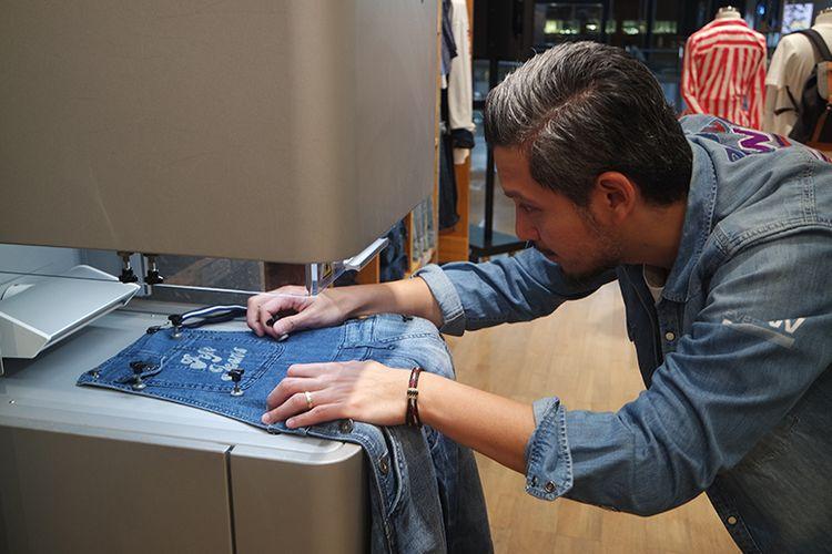 Senior Brand Manager Pepe Jeans London, Olaf Djanuismadi saat mendemonstrasikan penggunaan mesin laser Custom Studio di Pepe Jeans London Grand Indonesia Jakarta, Jumat (23/8).