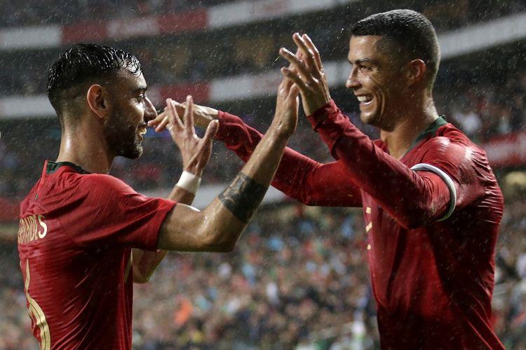 Bruno Fernandes (kiri) dan Cristiano Ronaldo (kanan) merayakan gol pada pertandingan persahabatan antara Portugal dan Aljazair, 7 Juni 2018 di Stadion Luz, Lisbon.