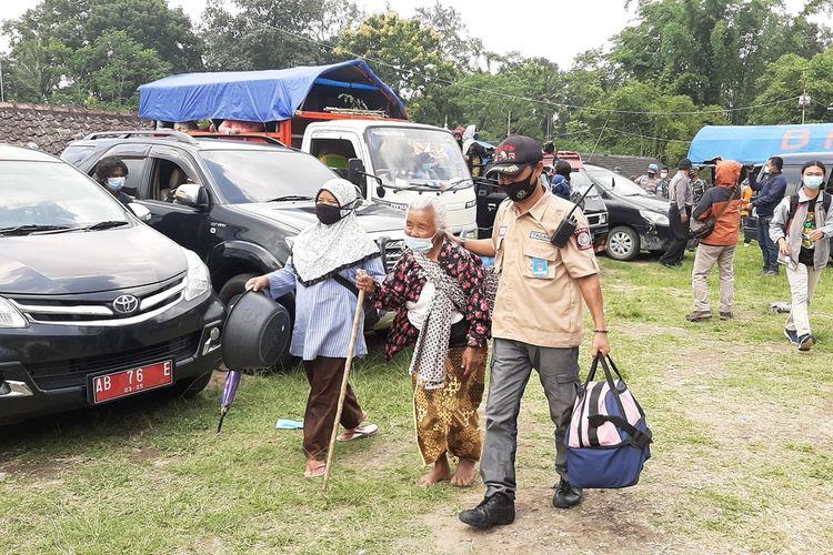 Salah satu pengungsi Merapi berusia lanjut saat dibantu menuju armada yang akan mengantar kembali ke rumahnya di Kalitengah Lor.