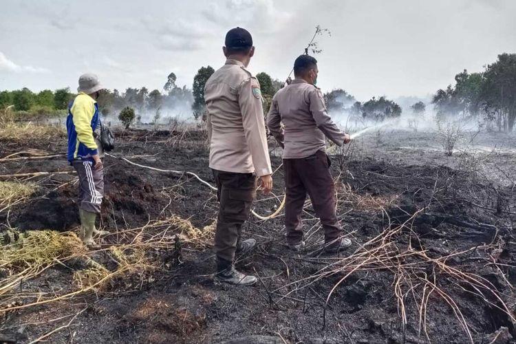 Petugas Polsek Rangsang melakukan pemadaman api karhutla yang terjadi di Desa Wonosari, Kecamatan Rangsang, Kabupaten Kepulauan Meranti, Riau, Senin (8/2/2021). Dalam kasus ini, petugas menangkap satu orang pelaku yang membakar lahan tersebut.