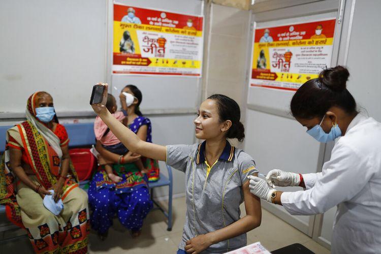 Seorang wanita India berswafoto saat petugas kesehatan memberikan vaksin Covid-19 di Rumah Sakit Wanita Pemerintah Distrik di Varanasi, India, Sabtu, 28 Agustus 2021.