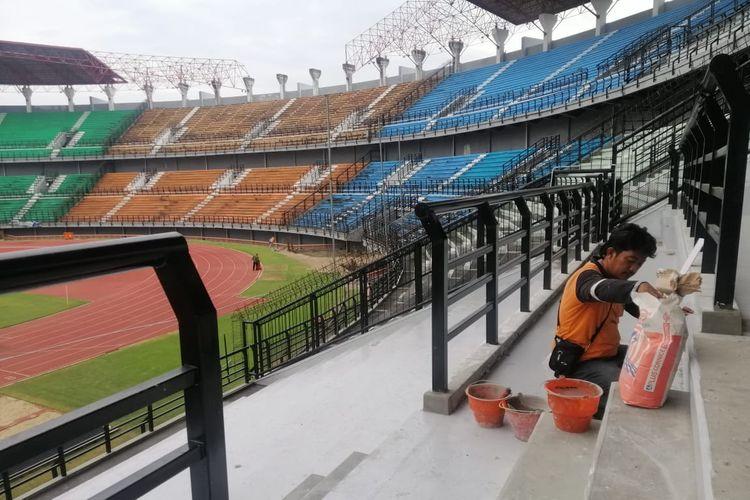 Seorang pekerja sedang melakukan pembenahan tribun Stadion Gelora Bung Tomo Surabaya sebagai persiapan Piala Dunia U-20 2021.