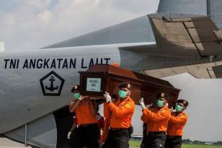 Petugas Basarnas mengangkat peti berisi salah satu dari tiga jasad penumpang AirAsia QZ8501 yang dikirim ke Surabaya, Jawa Timur, Sabtu (17/1/2015).