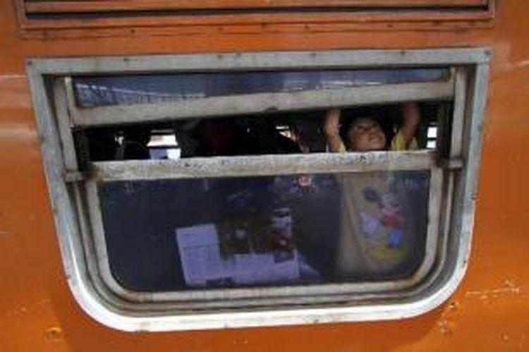 Seorang anak mencoba membuka jendela kereta ekonomi Kertajaya, tujuan Stasiun Pasar Turi, Surabaya, saat mudik bersama keluarga dari Stasiun Senen, Jakarta, Sabtu (11/8/2012).