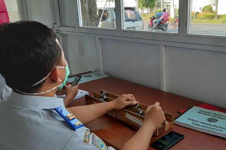 Salah seorang petugas dari Dinas Perhubungan Kabupaten Pekalongan, Jawa Tengah menghitung kendaraan yang melintas di jalur pantura.