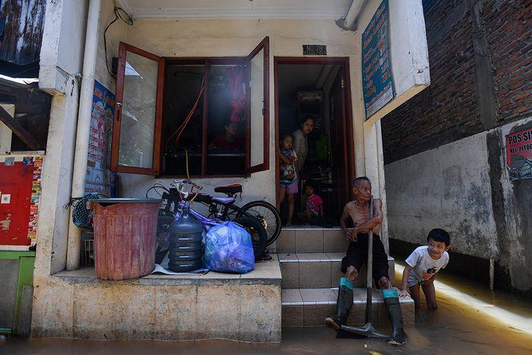 Warga menunggu air surut saat banjir melanda kawasan permukiman di Petogogan, Kebayoran Baru, Jakarta Selatan, Senin (5/10/2020). Banjir tersebut terjadi akibat meluapnya Kali Krukut.