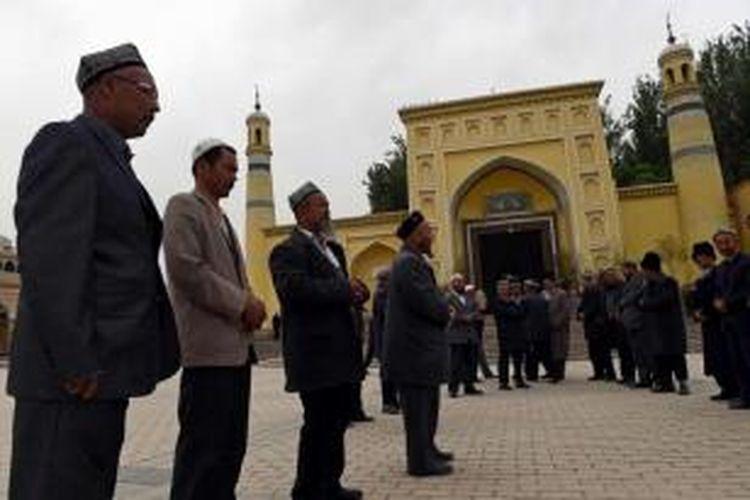 Warga Suku Uighur berkumpul usai menjalankan shalat di Masjid Id Kah di Kashgar, Xinjiang, China bagian barat, 19 April 2015. Pihak berwenang China telah membatasi ekspresi agama di Xinjiang, yang telah memicu perlawanan.
