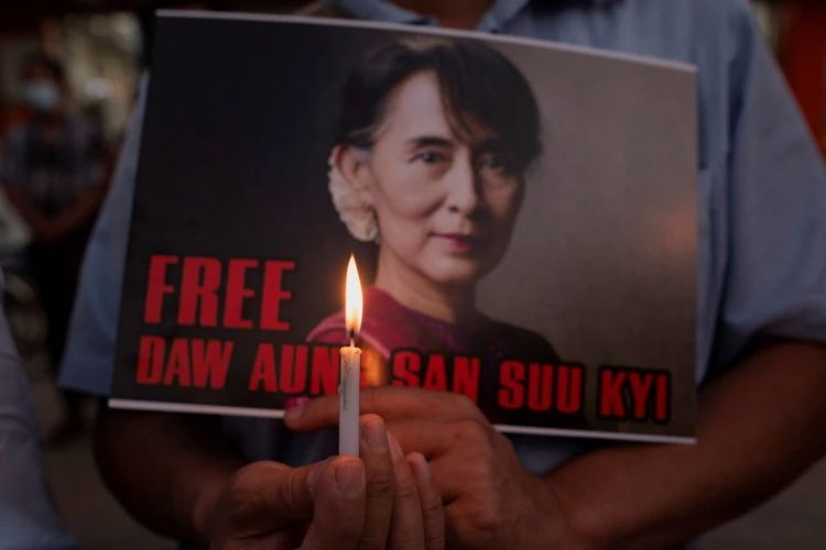 Seorang demonstran memegang plakat dan lilin selama protes menentang kudeta militer di Yangon, Myanmar, 16 Februari 2021.