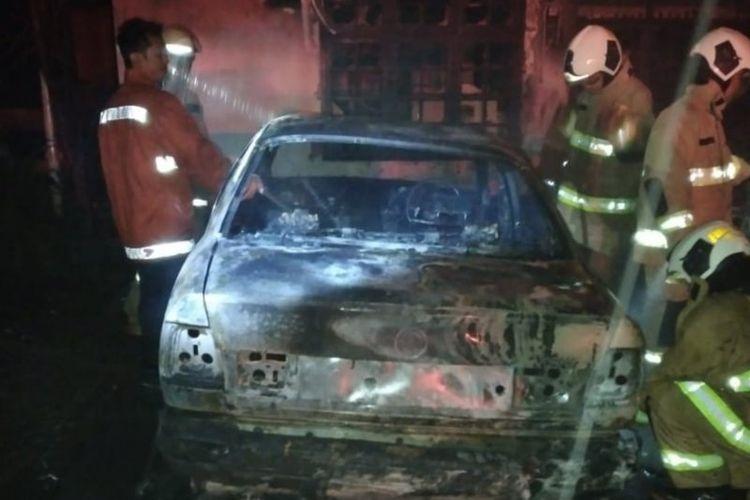 Petugas Damkar Jakarta Timur memadamkan api yang membakar salah satu mobil sedan di kawasan Kayu Putih, Pulogadung, Kamis (12/3/2020) dini hari. Petugas menemukan dua benda mirip dengan bom molotov yang diduga menjadi sumber percikan api.