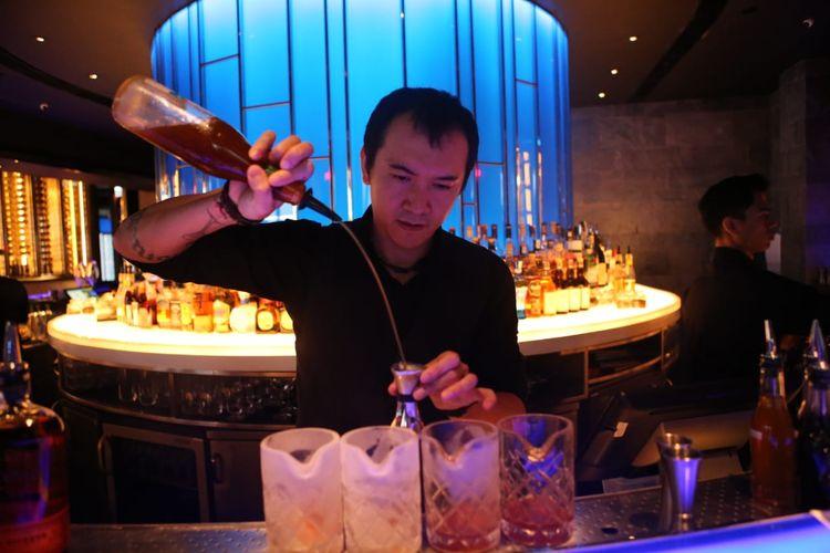 Richard Charles sedang berkreasi di balik bar untuk membuat racikan koktail di restoran Hakkasan, Jakarta.