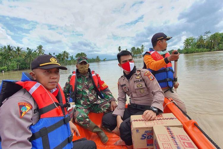 Polisi menyeberangi lokasi banjir di Desa Lawang, Kecamatan Matangkuli, Kabupaten Aceh Utara, Senin (18/5/2020)