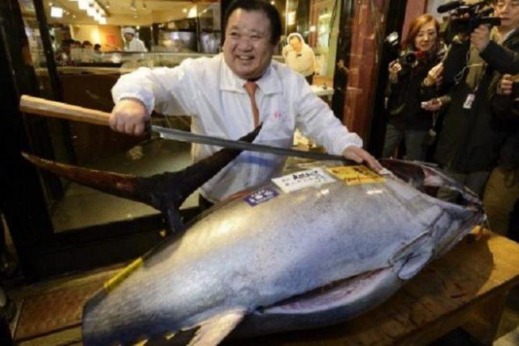 Kiyoshi Kimura, Presiden Kiyomura KK, berpose dengan ikan tuna seberat 180 kilogram, yang dibeli seharga 4,51 juta yen dalam lelang tahun baru tahunan di pasar ikan Tsukiji, Tokyo, Senin (5/1/2015).