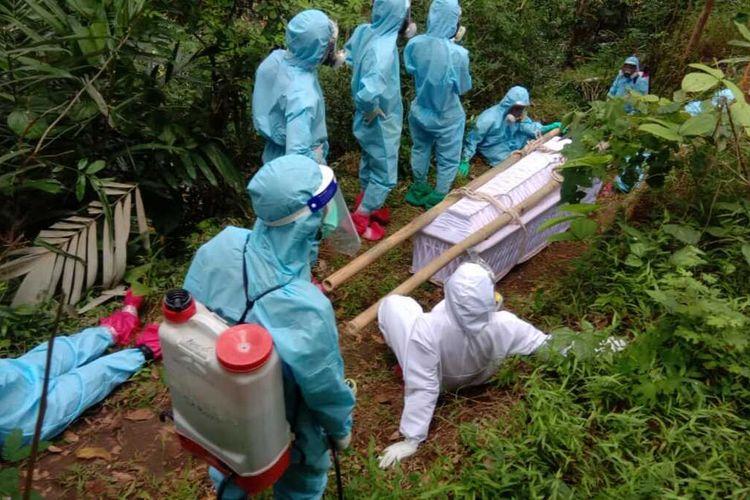Pemakaman dengan protokol Covid-19 untuk seorang warga di Pedukuhan Pntog Kulon, Banjaroyo, Kapanewon Kalibawang, Kulon Progo, Daerah Istimewa Yogyakarta. Relawan pemakaman naik turun bukit dan lewat sungai untuk menuju lokasi pemakaman umum warga.