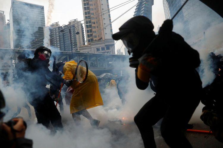 Para peserta demo Hong Kong ketika menghindari gas air mata dari polisi Minggu (25/8/2019).