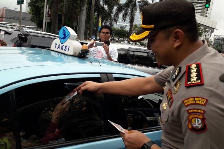 Kapolres Jakarta Barat Kombes Pol Hengki Haryadi membagikan mawar dan stiker sebagai simbol kampanye anti hoaks di jalam S. Supratman, Slipi, Jakarta Barat pada Senin (12/3/2018)
