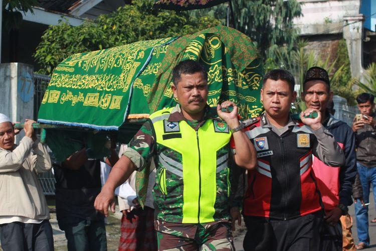 Personil TNI/Polri membantu membawa keranda Ane Liane (22), petugas KPPS 28 Desa Cimacan, Kec. Cipanas, Kab.Cianjur, Jawa Barat yang meninggal karena kelelahan ke tempat peristirahatannya yang terakhir, Jumat (26/04/2019).